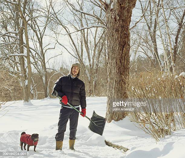 Man standing in snow with dog, holding shovel, portrait