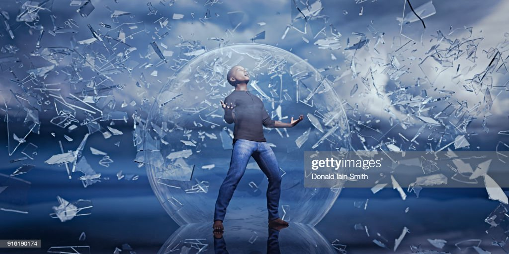 Man standing in sphere protected from falling shards of glass : Foto de stock