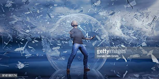 Man standing in sphere protected from falling shards of glass