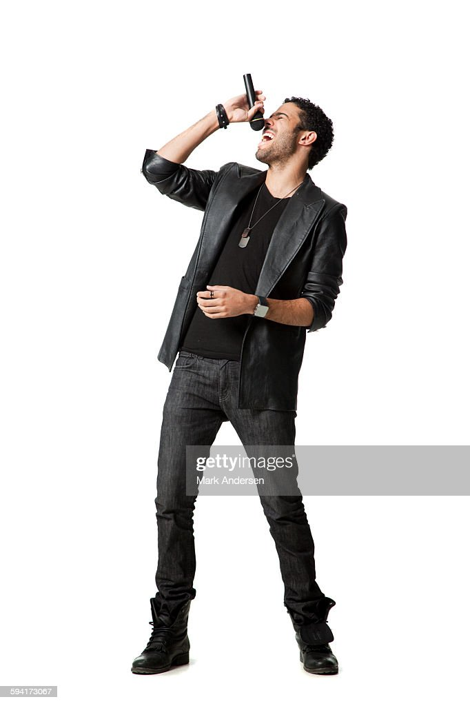 Man standing in studio singing into microphone : Foto de stock
