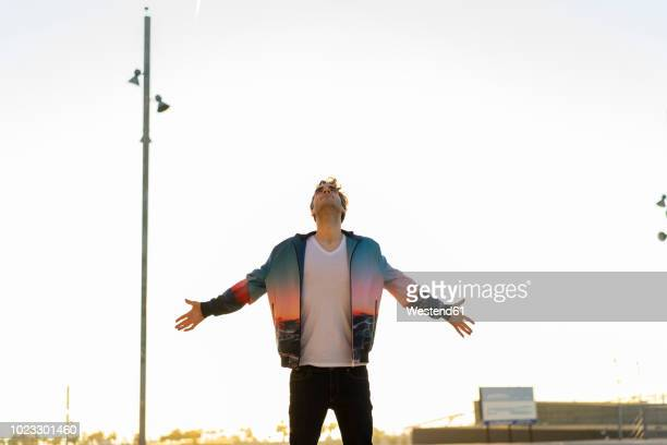 man standing in the city with arms outstretched, looking up - arms outstretched stock pictures, royalty-free photos & images