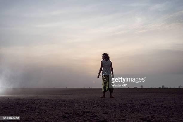 Man standing in the desert watching sunrise