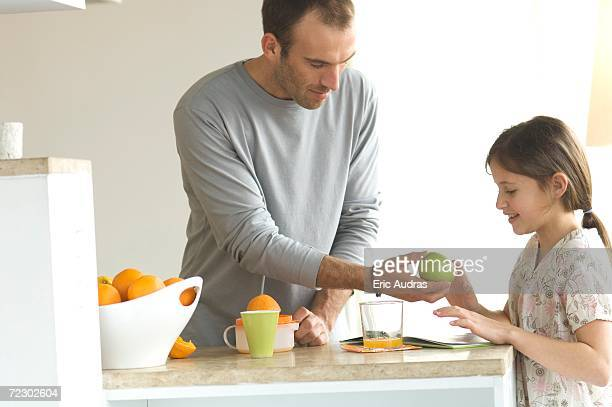 Man standing in the kitchen, giving an apple to little girl