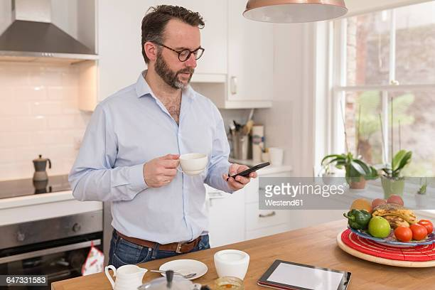 man standing in the kitchen with cup of coffee looking at his smartphone - einzelner mann über 40 stock-fotos und bilder