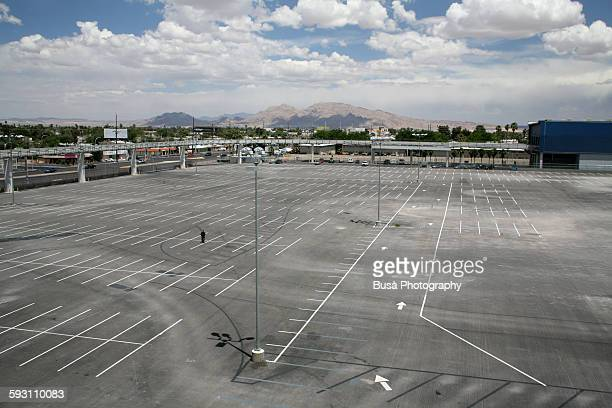 Man standing in the middle of an empty parking lot