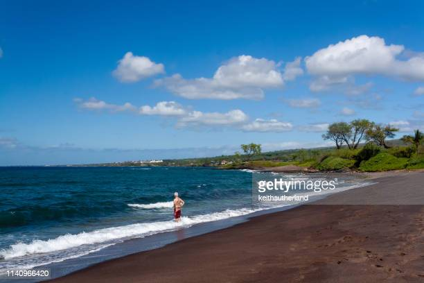 man standing in the ocean surf on black sand beach, maui, hawaii, united states - punalu'u_beach stock pictures, royalty-free photos & images