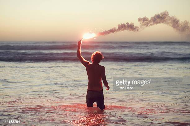 man standing in the ocean with burning flare