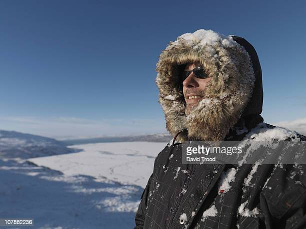 man standing in the snow in greenland - parka coat stock photos and pictures