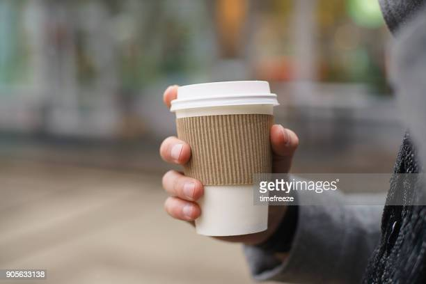 man standing in the street holding a cup of coffee - kaffee getränk stock-fotos und bilder