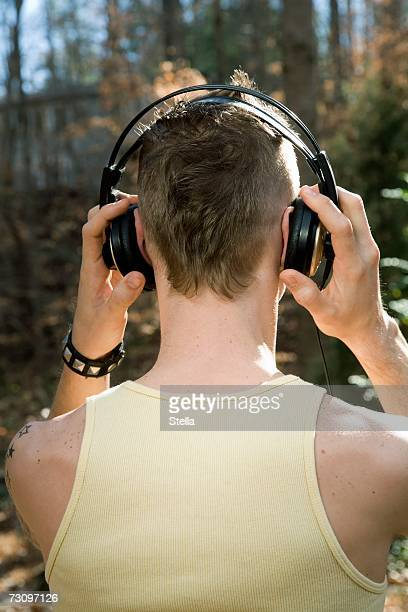 Man standing in the woods and wearing headphones