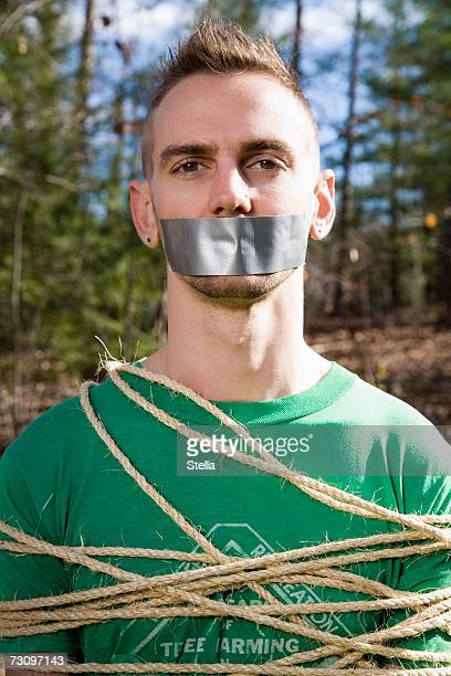 Man standing in the woods bound in rope and with adhesive tape covering his mouth
