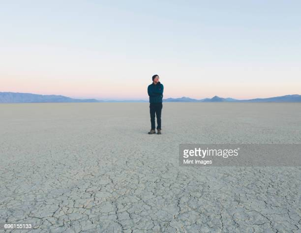 Man standing in vast desert playa at dawn, Black Rock Desert, Nevada