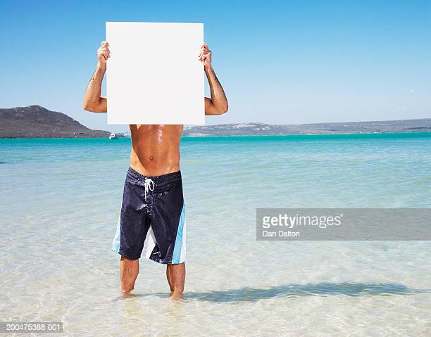 Man standing in water, holding blank white board in front of face