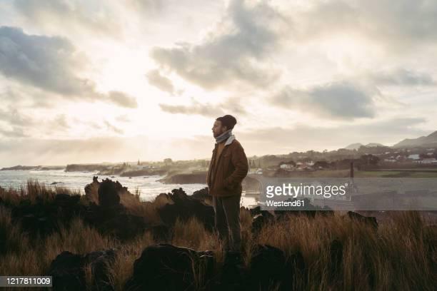 man standing in wild landscape at the coast, sao miguel island, azores, portugal - las azores fotografías e imágenes de stock