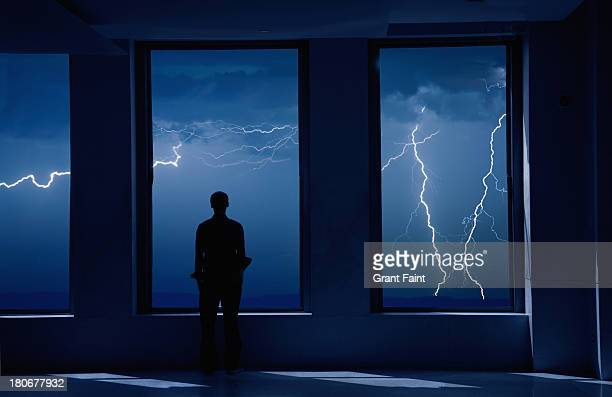 Man standing in window during storm.