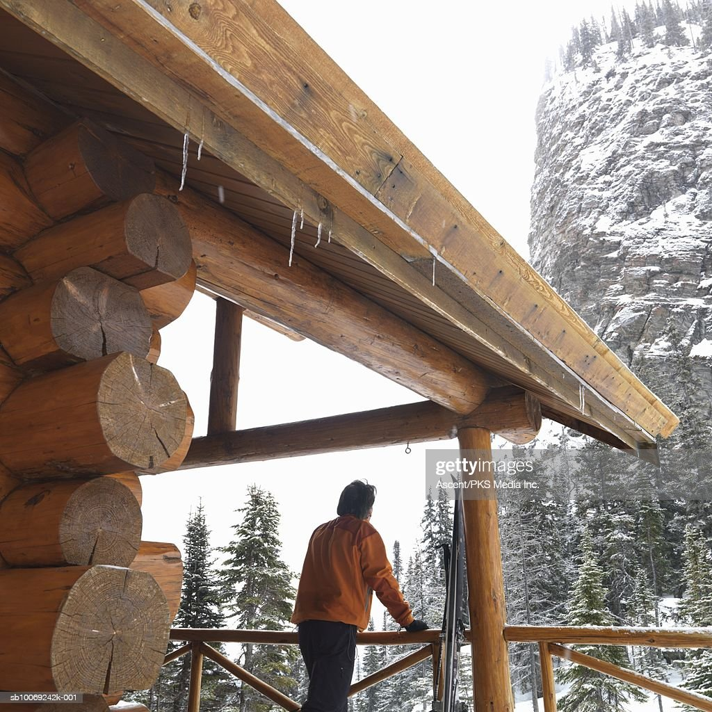 Man standing in wooden hut looking at mountains, rear view : Stockfoto