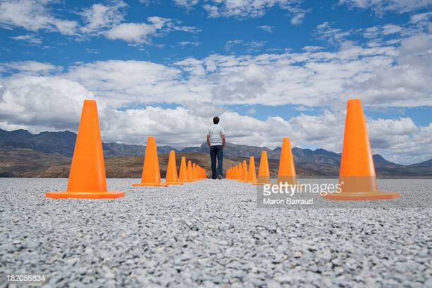 Man standing in-between two rows of safety cones