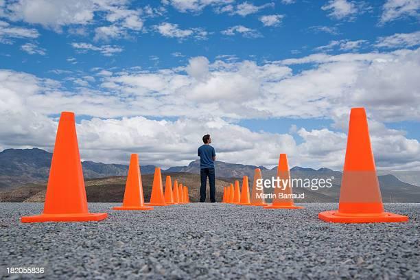 Mann stehend im zwischen zwei Reihen Sicherheit Hütchen