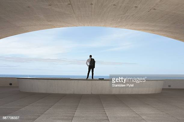 Man standing inside a building looking at ocean