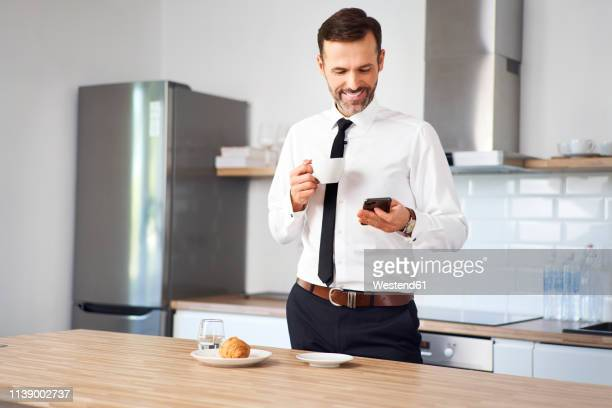 man standing int he kitchen  in the having coffee and looking at his phone before work - よそいきの服 ストックフォトと画像