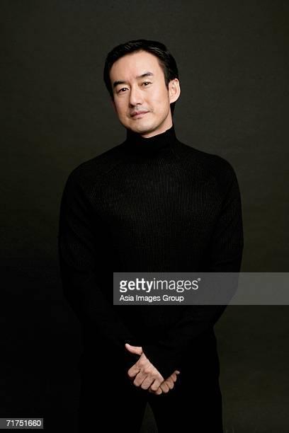 man standing, looking at camera, black background - タートルネック ストックフォトと画像
