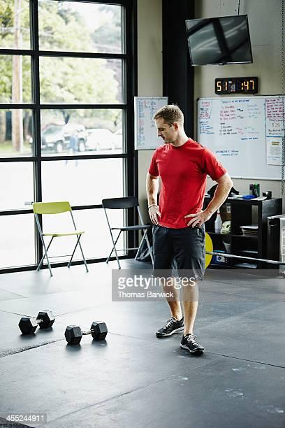 Man standing looking at dumbbells on floor in gym