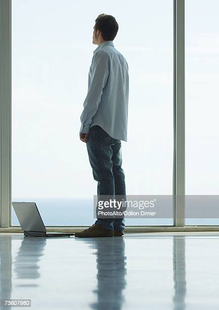 Man standing, looking out bay window, laptop on floor next to him