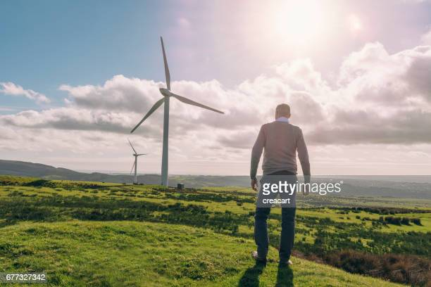man standing looking out over countryside with wind turbines.