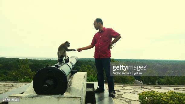 Man Standing Monkey Sitting On Cannon Against Sky