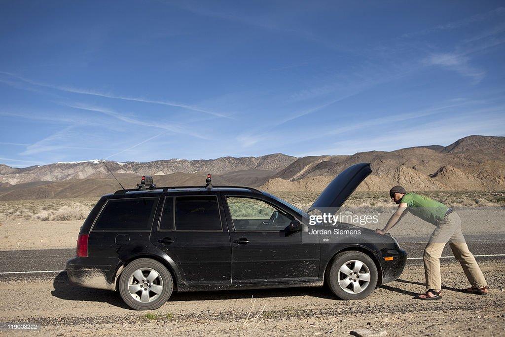 Man standing near a broke down car. : Stock Photo