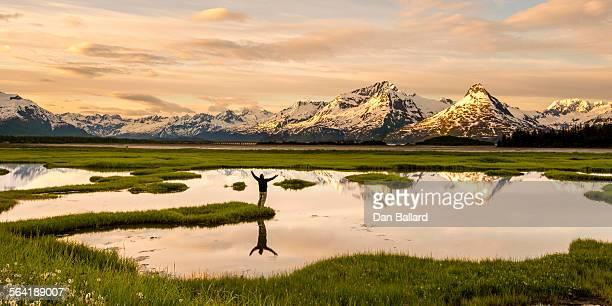 a man standing near a pond looking torward a mountain range. valdez, alaska, usa. - paisajes de alaska fotografías e imágenes de stock