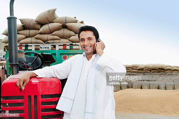 man standing near a tractor talking on a mobile phone, anaj mandi, sohna, gurgaon, haryana, india - loading stock pictures, royalty-free photos & images