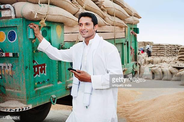 Man standing near a trailer holding a mobile phone, Anaj Mandi, Sohna, Gurgaon, Haryana, India