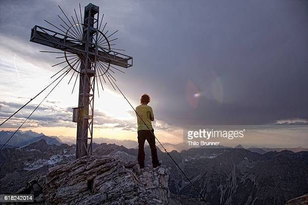 Man standing near cross on top of mountain and looking at view