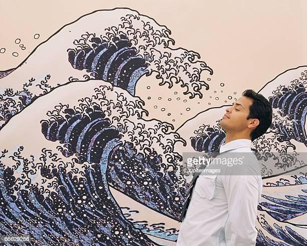 Man standing near mural of waves