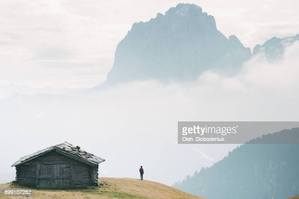 man standing near the hut with view of dolomites mountains, italy - shack stock pictures, royalty-free photos & images