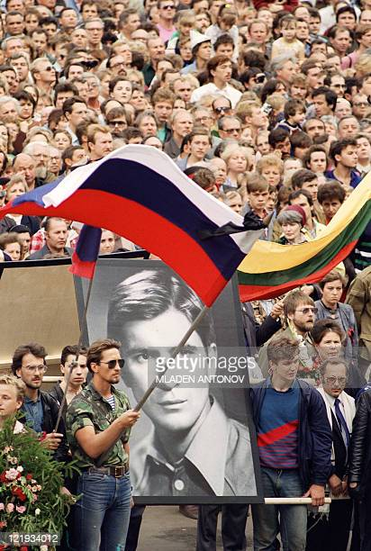 A man standing near the portrait of Vladimir Ussov one of the three victims of this week's coup waves a flag during the funeral procession in central...