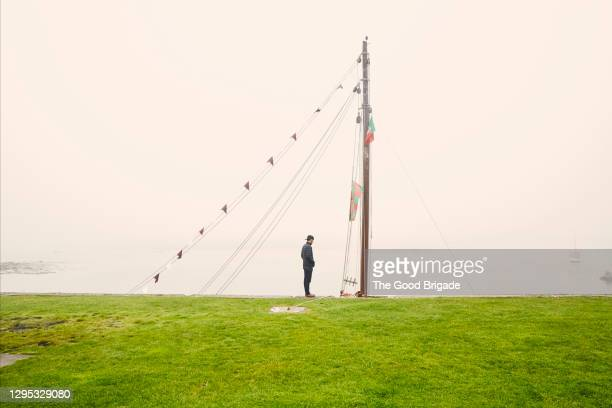 man standing near the waters edge in galway, ireland - hands in pockets stock pictures, royalty-free photos & images