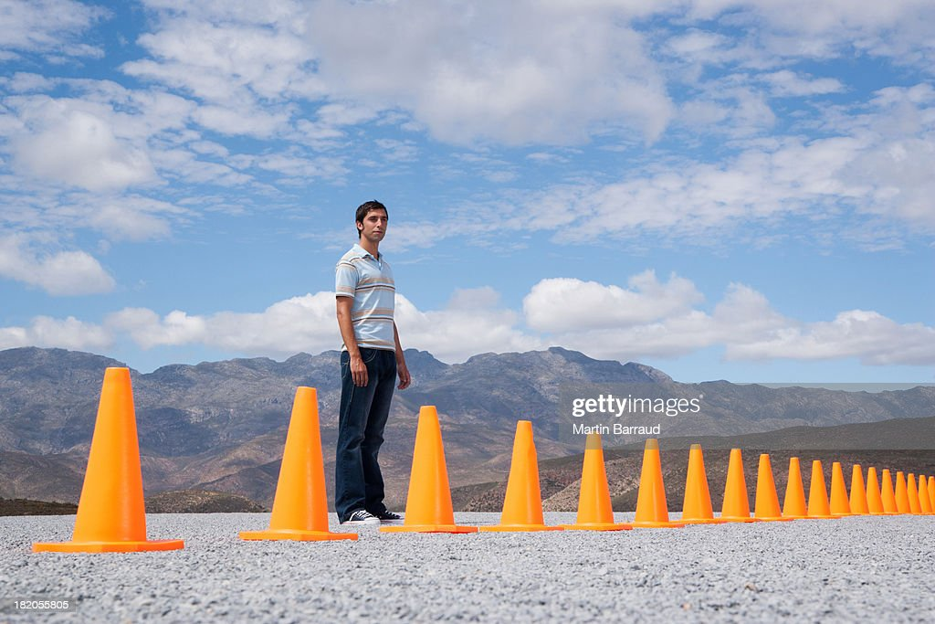 Man standing near traffic cones in outdoors   : Stock Photo