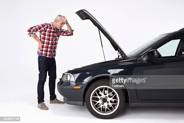 a man standing next to a broke down car, looking down at engine in frustration - broken down car stock pictures, royalty-free photos & images