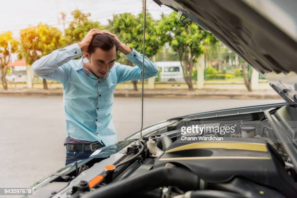 A man standing next to a broke down car, looking down at engine in frustration