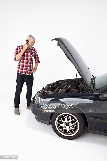 A man standing next to a broke down car while using a cell phone