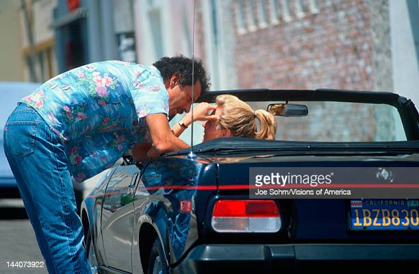 A man standing next to a car talking to a woman