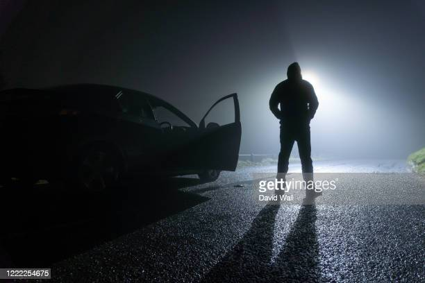 a man standing next to a car, with door open, parked on the side of the road, underneath a street light. on a foggy winters night - criminal stock pictures, royalty-free photos & images