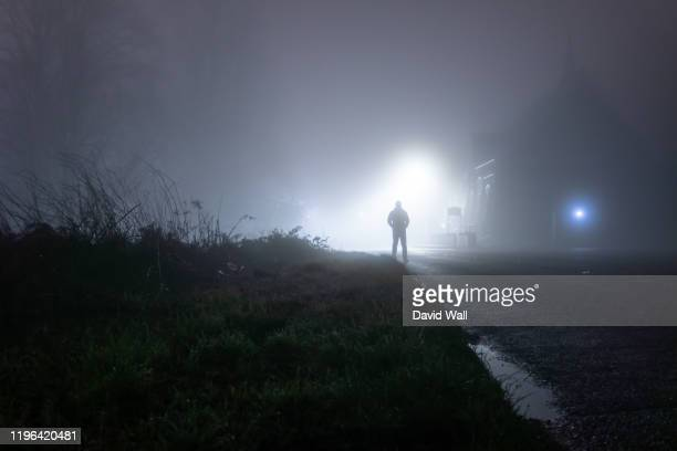 a man standing next to a church, underneath a street light, on a spooky, scary, rural, country road. on a foggy winters night - paranormal stock pictures, royalty-free photos & images