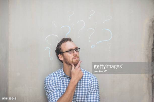 man standing next to a concrete wall with chalk question mark drawings - mano en la barbilla fotografías e imágenes de stock