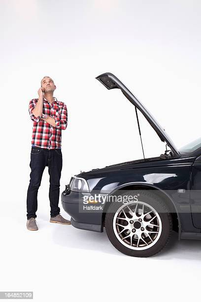 A man standing next to broke down car, using a cell phone and looking impatient