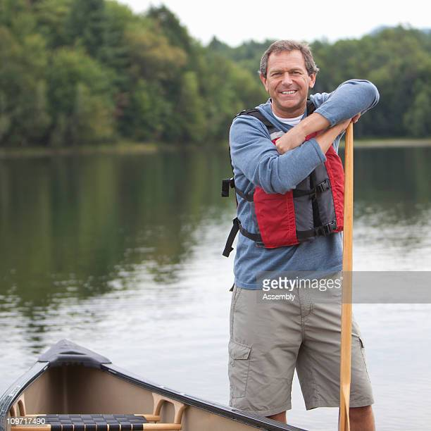 Man standing next to canoe on shore of lake
