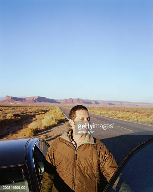 Man standing next to car on side of road, smiling
