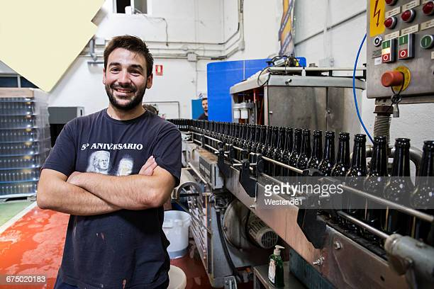 Man standing next to conveyor belt in bottling plant